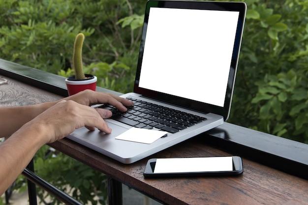 Макет руку человек использовать ноутбук и кредитную карту на столе с телефоном на столе.