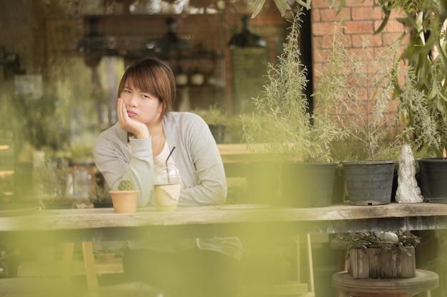 コーヒーショップで氷のコーヒーを持つ美しい女性