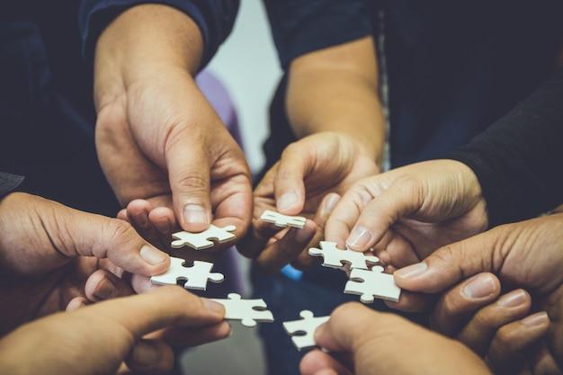 手持ちのジグソーパズルのチームワークグループ。ビジネスコンセプトアイデア