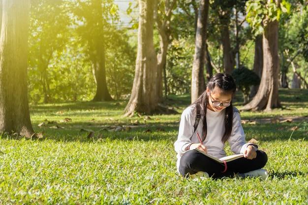 公園で本を探しているメガネの十代の少女