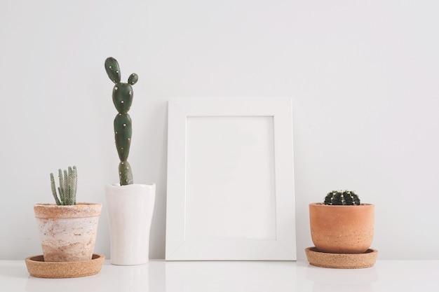 棚の上に白い背景の粘土の鉢のサボテンとフレームの写真をモックアップ。