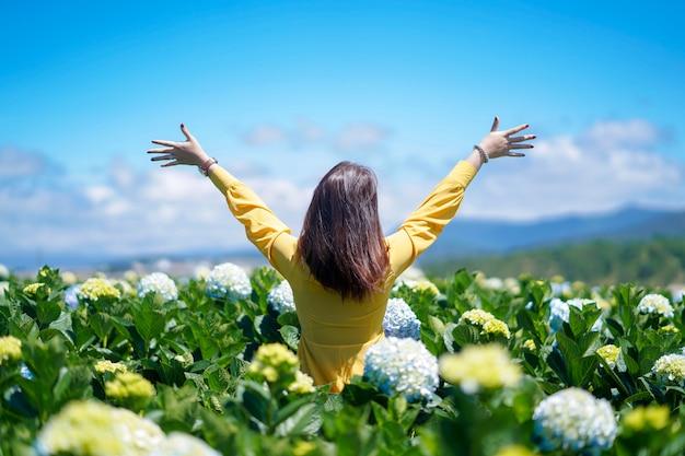 幸せなアジアの女性は、アジサイの花のフィールドで彼女の手を保持しています。