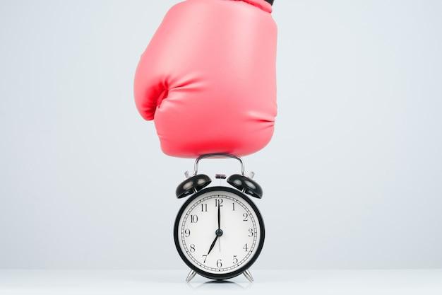Красные боксерские перчатки, пробивающие классический будильник.
