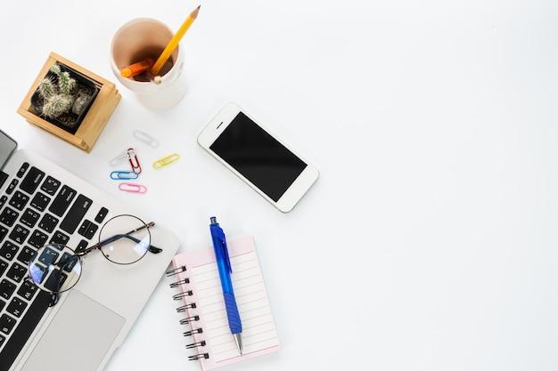 コーヒーカップ、ノートブック、スマートフォン、キーボードとオフィスデスクワークスペースのトップビュー