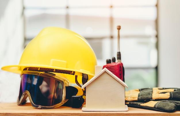 黄色のヘルメットと付属品は木製の床に置かれています