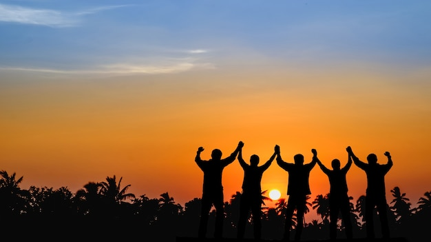 成功を分かち合うために喜んでチームが一緒に立って、日没の手を見る。