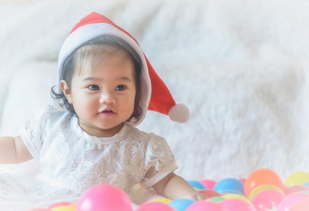 小さな女の子、サンタクロースの帽子は、彼女のベッドとカラフルなボールで遊んでいます。
