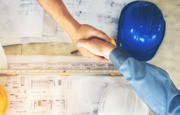 建築家、エンジニア、ビジネスマンは、団結のために手に参加しています。