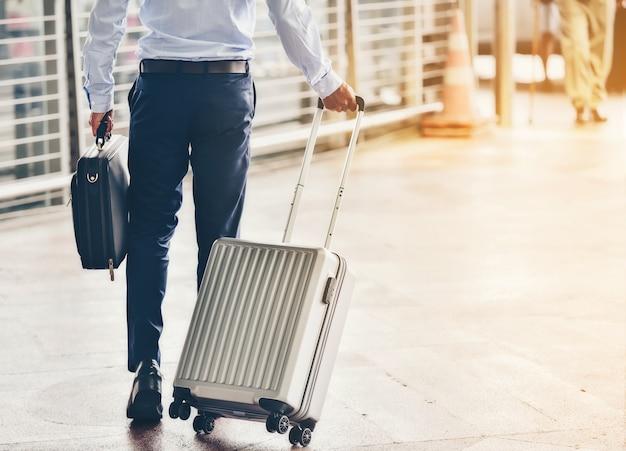 ビジネスマンは荷物を空港に持ち帰ります。
