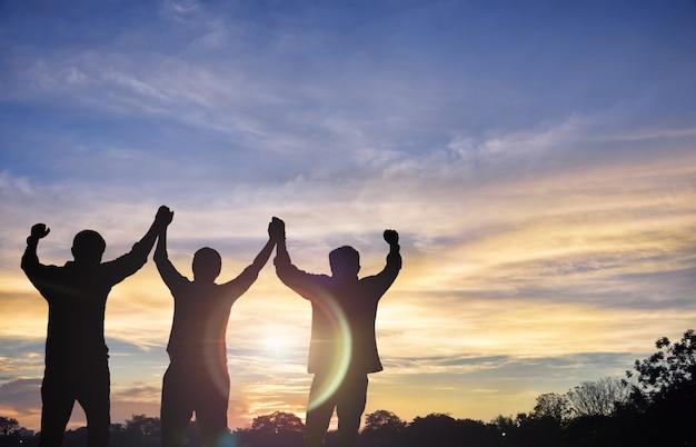 成功を共有しようとしているチームが一緒に立って、日没の背中を手にしてください