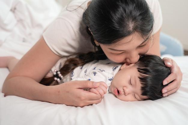 優しく愛してベッドで寝ている赤ちゃんにキスして触れるアジアの母