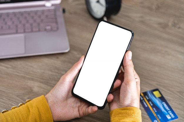 オフィスの机の上の空白の画面とクレジットカードで携帯電話を保持している女性の手