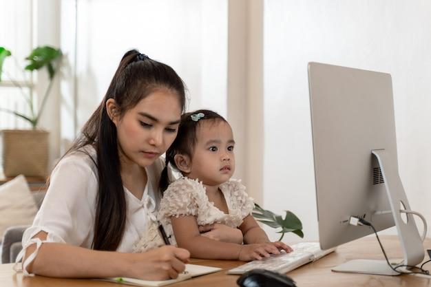 Азиатская молодая мать работает из дома и держит ребенка