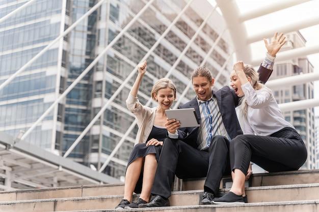 Группа деловых людей, работающих и обсуждающих что-то положительное со своим зрелым коллегой и использующих планшет на улице в столице