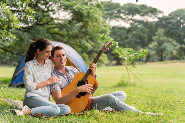 Время пикника и кемпинга. молодая пара весело с гитарой на пикник и кемпинг в парке.
