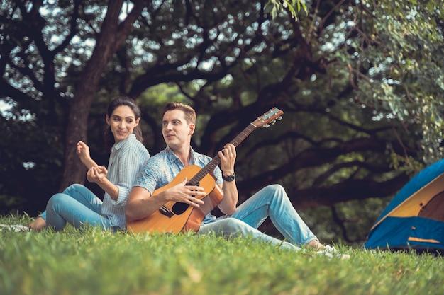 Время пикника и кемпинга. молодая пара весело с гитарой на пикник и кемпинг в парке. любовь и нежность, романтик играет на гитаре своей девушке, концепция образа жизни