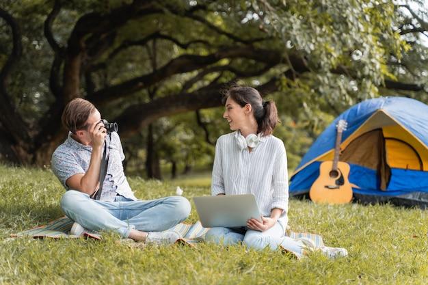 若いカップルは芝生のフィールドに座って写真を撮り、コンピューターをプレイします。自然と美しい木々の中でキャンプしながら幸せに休みます。