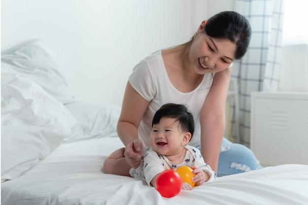 ベッドの上のアジアの赤ちゃんと白いボールの上で一緒におもちゃのボールを遊んで幸せで陽気な気持ちとベッドの上でクロールする赤ちゃんを持つ若い美しいアジアの母。赤ちゃん家族の概念