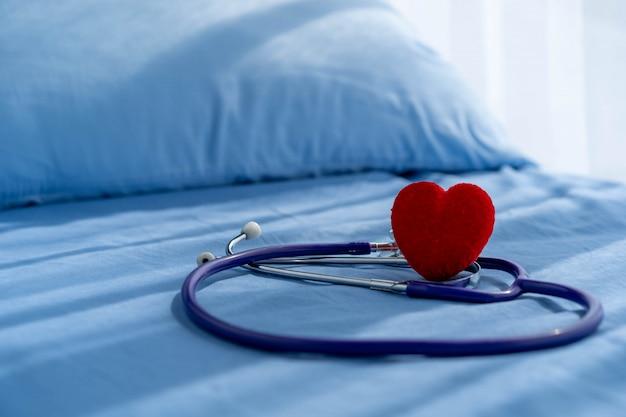 医学の聴診器と患者のベッドの上の赤いハート。