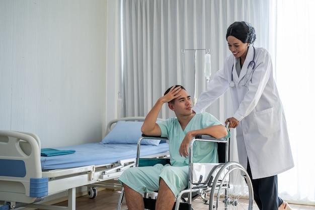 Афро-американский врач толкает инвалидную коляску и предоставляет консультации относительно лечения пациентам, сидящим в инвалидной коляске, и внимательно следит за