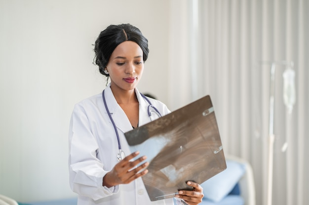 Афро-американский женщина-врач, глядя на рентгенографии в комнате пациента