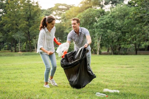 Любители-добровольцы вместе в перчатках собирают мусор в парке, чтобы сохранить окружающую среду в чистоте