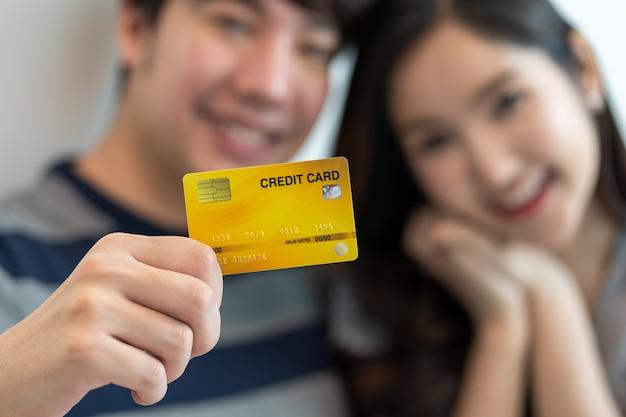 座っている間にラップトップコンピューターでオンラインショッピングアジアの陽気なカップルの肖像画。クレジットカードを持っている人
