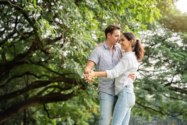 ピクニックとキャンプの時間。公園で愛の瞬間に楽しんでいる若いカップル。愛と優しさ、彼のガールフレンド、ライフスタイルのコンセプトにギターを弾くロマンチックな男