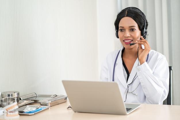 Портрет доктора в наушниках советуя с телефоном по телефону