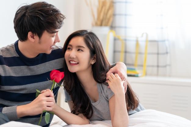 Романтичный человек давая розу к красивой женщине, красивая элегантная азиатская пара обнимает и усмехается в спальне.