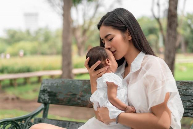 彼女の新生児を保持しているアジアの若い美しい母親は寝ており、愛を感じ、穏やかに触れてから公園の緑の芝生に座っています。