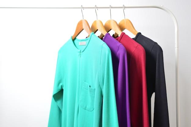 マルチカラーの女性のシャツ、ストライプ、ハンガー、白い背景