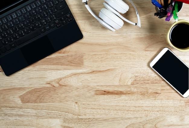 ホワイトヘッドホンと木製作業台のキーボード