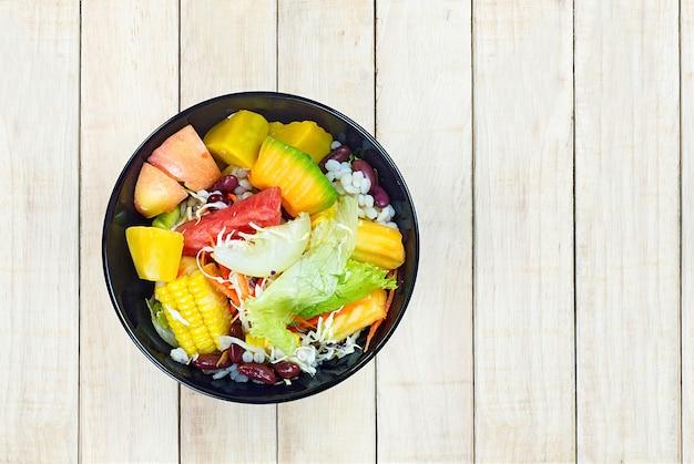 黒のボールで野菜と果物のサラダを混ぜて、木製テーブルのバックラウンドに置く