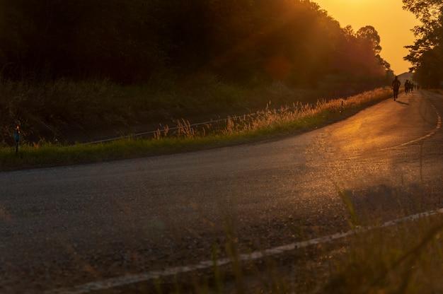 ぼやけた男は太陽の光の中で路上でジョギングします。
