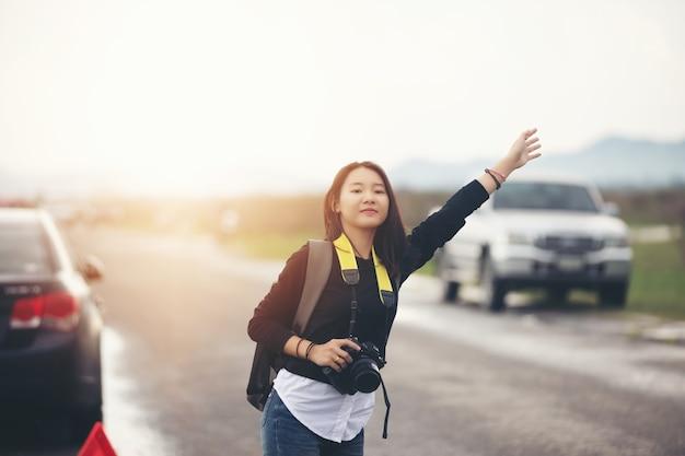女性は道端で腕を上げて立っている。車の故障後