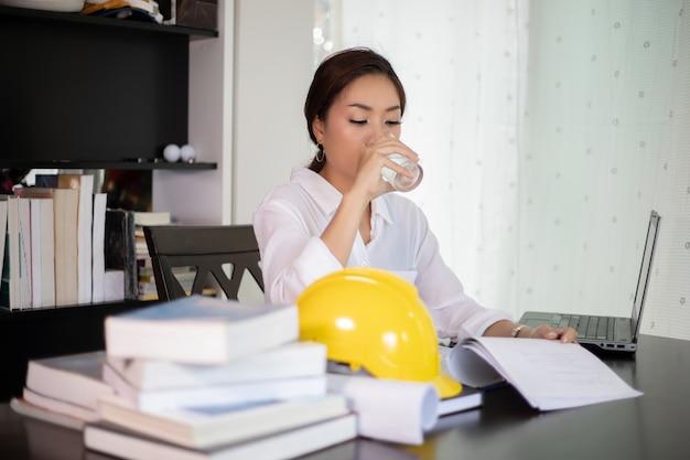 アジアの女性のエンジニアは水を飲んでおり、就任しています