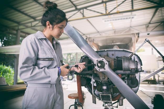 Азиатские женщины инженеры и техники ремонтируют самолеты.