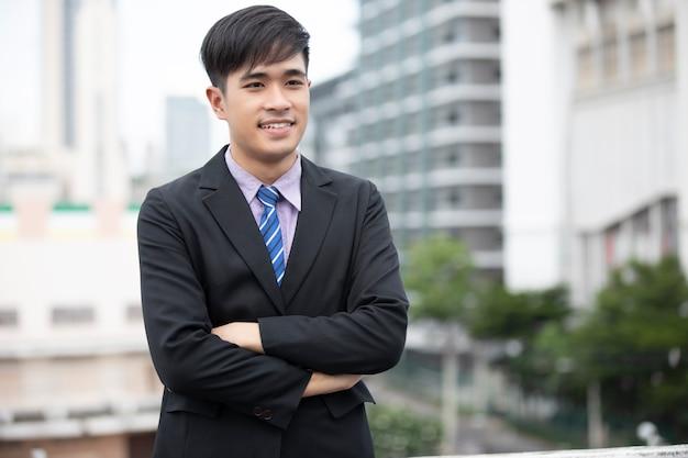 立って、屋外で笑顔で幸せハンサムなビジネスマン
