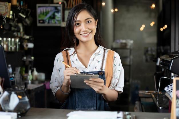 アジアの女性バスタコーヒーショップカウンターで笑い、コーヒーマシンを使用して