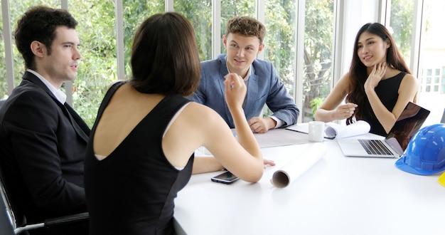 ビジネスマンとエンジニアが会議で文書やアイデアを議論するためのノートブックを使用