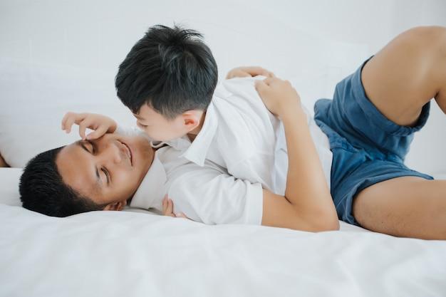 息子と一緒に幸せなアジア人の家族が寝室で遊んで笑う
