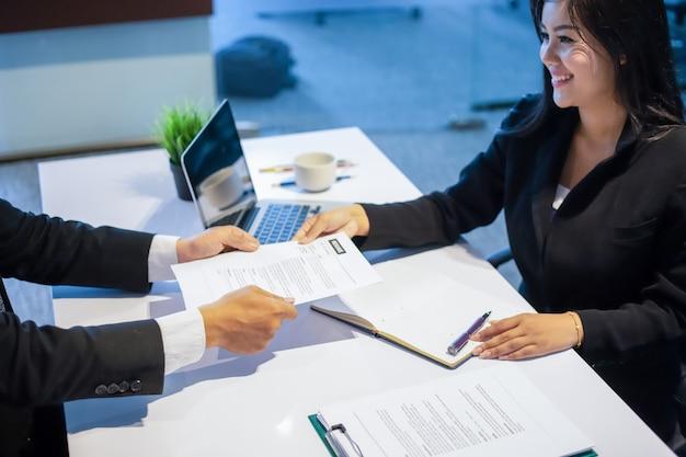 ビジネスインタビューの概念のための文書を議論するビジネスマンと経済婦