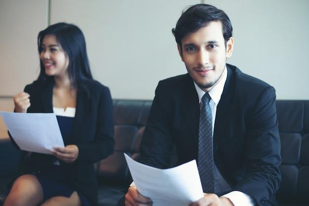 ビジネスマンと経済学者が会議や就職のコンセプトで文書やアイデアを話し合う