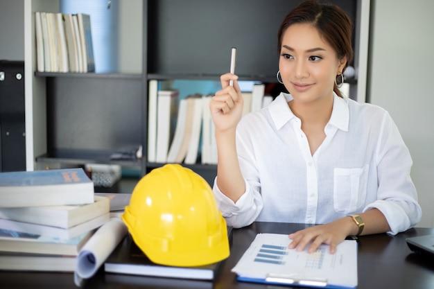 女性のエンジニアは新しい仕事を創造しようと考えており、笑顔で働いています