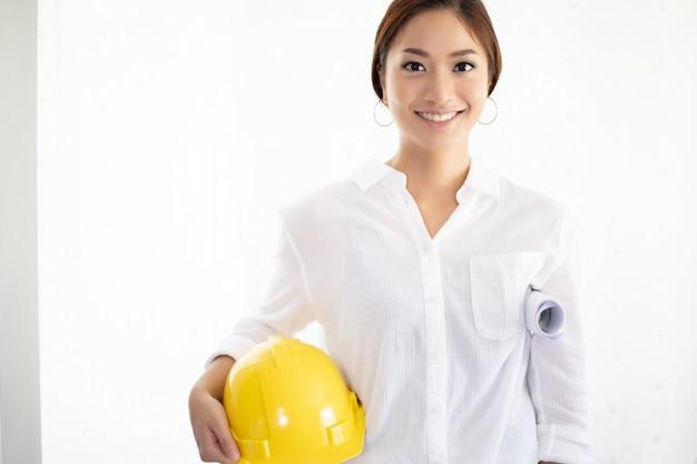 Азиатские женщины инженерные проверки и работы и проведение чертежи в офисе