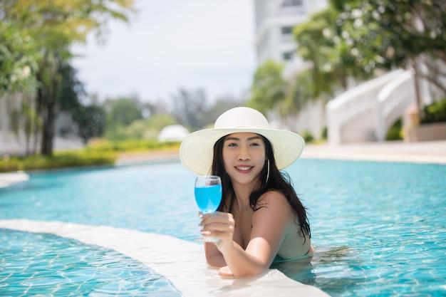 女性はスイミングプールで暑い夏にビキニを着用し、カクテルを飲む。