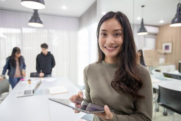アジアの女性学生笑顔でスマートフォンやタブレットを使って楽しんで