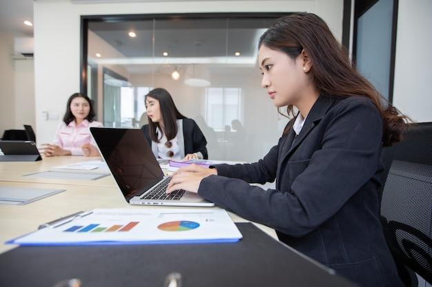 仕事とノートブックを使用して深刻なアジアの実業家