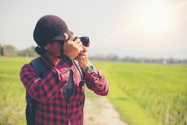 アジアの男性のバックパックと一緒に歩いて幸せな旅行者は山で写真を撮っています。